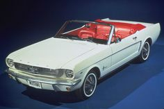 1964 1/2 Mustang convertible in Wimbledon White and Candy Apple Red Interior. Note that the grille does not have the horizontal bars running from each side of the corralled Mustang . . . a theme that never made it into production.