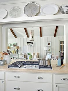 Plates are displayed on a shelf above the cooktop in this white cottage-style kitchen on HGTV.com.