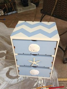Bought basic wood drawers from craft store.  Paint outside antique white chalk paint - drawers Louie Blue.  Chevron on top is easy  - draw a grid then use this to draw your lines.  Paint freehand.  Use a heavy duty cement to attach sandollars and star fish and voila!  $35 plus paint.