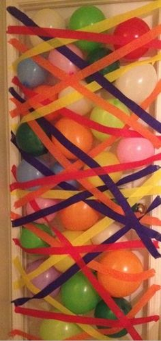 Balloon avalanche made out of balloons and streamers in doorway cute for surprise birthday party or the morning of someone's birthday