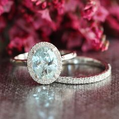Delicate and feminine, this wedding ring set showcases an aquamarine engagement ring with a 9x7mm oval shaped natural aquamarine set beautifully in