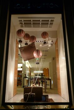 Balloons and suitcases in the window of Louis Vuitton