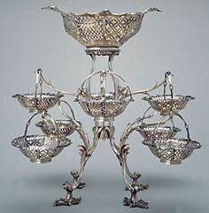 Silver Epergne, London, England, ca. 1771/2. Francis Butty and Nicholas Dumee (English, working, ca. 1758–1773), In May 1768, Arthur Middleton and his wife Mary Izard Middleton sailed abroad on a three year grand tour of Europe. When they returned to Charleston, they brought with them goods purchased during their travels, including over forty pieces of elegant plate. Among the silver was this outstanding epergne, with eight hanging baskets, all engraved with the Middleton coat of arms.