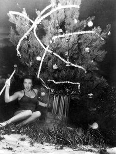 Mary Dwight displays croquet set gift she has just found under the underwater Christmas tree, 1948