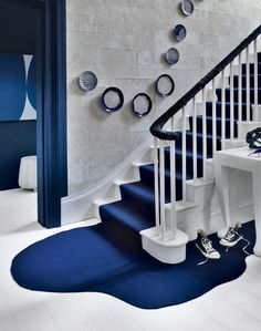 Get creative with carpet to make a dramatic entrance. This smart navy-and-white hallway is transformed by a bespoke deep-blue stair runner that seems to flow down the stairs to form a serene pool on the white wood floor below.