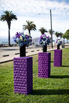 Fluffy violet and blue flowers placed upon purple pedestals made a unique altar arrangement! By Michael Daigian Design #weddings