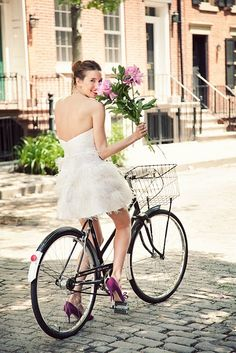 Girl in feather dress on bicycle #peonies #camillestyles #white