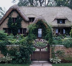 Straight out of a fairy tale, this 1920s brick-and-stone dwelling with mullioned windows and a wiggly Dr. Seuss-style roof is reminiscent of Cotswold cottages of the English countryside.