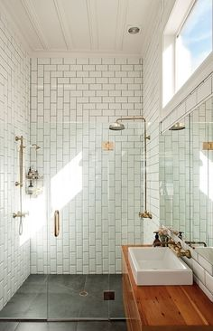 Modern bathroom with dual brass shower heads against a backdrop of white subway tiled walls highlighted by gray grout and laid in a concentric pattern within the frameless glass shower surround. Gray stone tiled floors unite the room alongside a wooden vanity with vessel sink with wall mounted brass faucet below a mirrored medicine cabinet. Love the tile pattern!