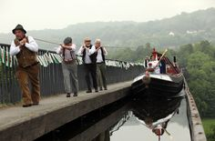 Joanne Gregory carries the Olympic torch on a hand drawn canal boat across the Pontcysyllte Aqueduct, a UNESCO World Heritage Site on May 30 in Llangollen, Wales. The Olympic flame is now on day 12 of a 70-day relay involving 8,000 torchbearers covering 8,000 miles. (Christopher Furlong/Getty Images)