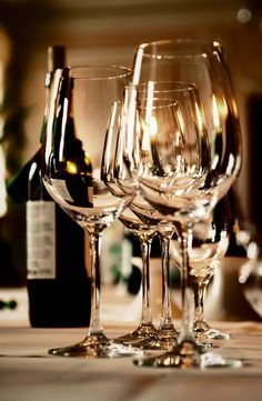 Wine glasses and a bottle on a table - luxury wine accessories at https://www.mimisfifis.com