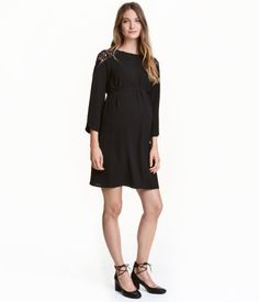 Black. Short dress in crêped fabric with lace at top. Ties below bust, opening at back of neck with button, and 3/4-length sleeves. Unlined.