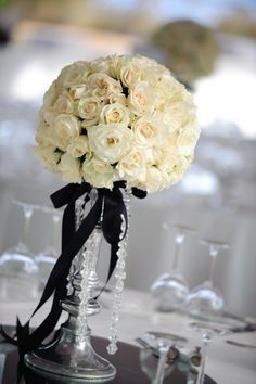 White rose pomander on a candlestick with black ribbon and crystals.