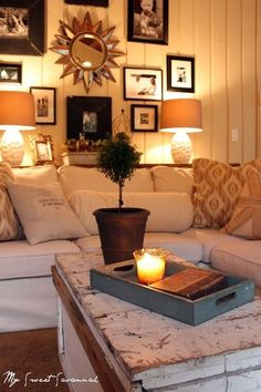 Looks so comfy and inviting! (Shelf behind couch w/ two lamps) love the way they hung random pictures too!