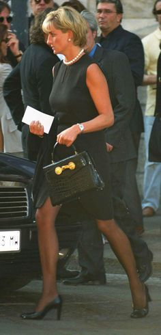 """22nd July 1997, Milan, Italy: """"The Princess of Wales was at Milan's gothic cathedralon 22 July 1997for the memorial service of her friend Gianni Versace, who once called her """"The Mother Teresa and Cindy Crawford of our time"""". She wears his black shift-dress and leather Kelly bag with Medusa heads, re-named """"the Diana bag"""". Diana comforted Elton John during the service. By a tragic twist of fate, he was to sing at her funeral service just a few weeks later. Comment: duchesseorange.."""