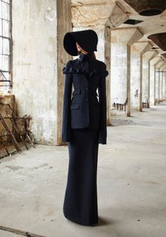 LOOK 1:  Black wool off the shoulder tailored jacket with ruffled neckline.  Black cotton poplin tailored shirt with high collar.  Black wool maxi skirt