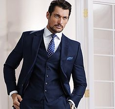 Man wearing navy three piece suit, white shirt and blue tie