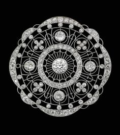 A Belle Époque diamond brooch.  Of circular design, the trellis-work set centrally with an old round brilliant-cut diamond, with a further four old round brilliant-cut diamonds to cardinal points, diamond-set floral motifs to mid-cardinal points, within diamond-set scalloped borders, width 48mm, the diamonds estimated to weigh approximately 4.75cts in total