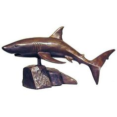 "Great White Shark Bronze Sculptures, have been carefully selected for the discerning buyer. This Great White Shark Bronze collection is ideal for galleries, upmarket retail shops and the interior decorator. Selected pieces are available in their natural bronze casting or silver plated. The artists have used the ""lost wax"" process in casting, which is the preferred method, as it brings out every little detail of the original sculpture.  Height: 30cm Length: 44cm GET @ www.auldco.co.za"