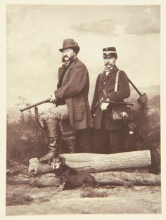 Photograph of Prince Augustus standing three-quarters left and wearing hunting costume with boots and hat. He has his left foot on a log and holds a gun. An attendant stands behind him, with a gun hanging from his shoulder. In the foreground stands a small dog. Painted landscape backdrop. 1864