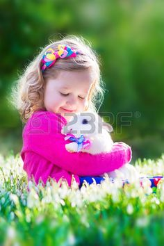 Adorable little girl, cute curly toddler in a colorful summer dress, playing with a real rabbit, having fun with her pet bunny in a beautiful garden with first spring snowdrop flowers