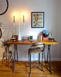 Old wrought-iron table legs were paired with a newly varnished piece of wood to make a practical desk. The antique stool and accessories give it a ton of elegant charm.
