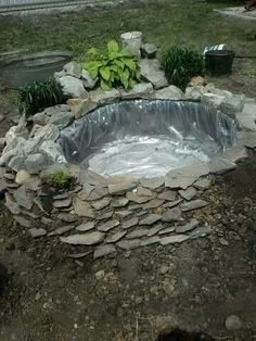 Little yard rock pool made out of a tire, plastic lining, and slate stones. Beautiful!