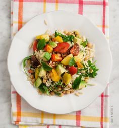 About 3 medium heirloom tomatoes, Olive oil, Sherry vinegar, 1/2 cup uncooked, whole wheat orzo, 1 clove garlic, A handful of arugula, 1/2 cup chickpeas, cooked and drained, 1/2 large avocado, diced, Juice of 1/2 a small lemon, Handful of fresh basil, Pine nuts (to taste), Salt and pepper