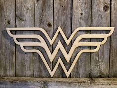 Wonder Woman wall hanging laser cut sign. (*Does not include fence panel background-- includes cutout sign only.) 20 wide X 9.6 tall X 1/4 thick. Rustic style unfinished wood comes ready to be painted or stained. *Please note: there may be slight color variations based on the cut of