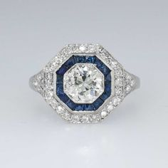 Gorgeous Art Deco Old European Cut Diamond & #Sapphire Ring Platinum | Antique & Estate Jewelry | SOLD: 1/8/15 JewelryFinds.com Price:$8300.00 The central sparkling old European cut diamond weighs an approximate 1.10cts and has the quality grade of J color, SI1 clarity. The ring has a hexagon shape with sparkle, a bit of blue beauty, and an era appropriate design. Around the diamond are 16 natural blue french cut gem quality sapphires