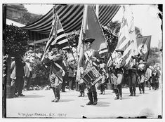 Men dressed up as Revolutionary War Drum and Fife Corps soldiers march down the street during a 4th of July parade in New York, 1911.
