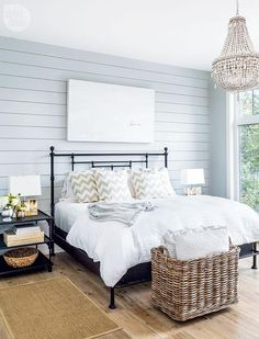 LVZ Design - Restful bedroom boasts a stunning blue shiplap wall holding a canvas print above an iron bed dressed in white bedding topped with gray chevron pillows lit by a RH Baby & Child Anselme Large Chandelier hung in front of the bed over a wicker storage basket.