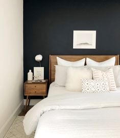 Black feature wall, white linen, midcentury modern side tables
