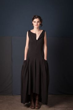 """This sleeveless, fitted dress is hand stitched using a single layer of our 100% organic medium-weight cotton jersey. The Julien Dress features hook and eye closures at the chest and gathered pockets below the hip. Measures 46"""" from shoulder to front hem and 53"""" from shoulder to back hem. Shown here in Black. Choose your color below. Please allow four to six weeks for delivery. Wash gently + Hang to dry. Free shipping. Made in the USA."""