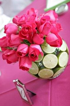 Simple yet beautiful use of color in this gorgeous centerpiece of fuchsia roses and limes...refreshing.