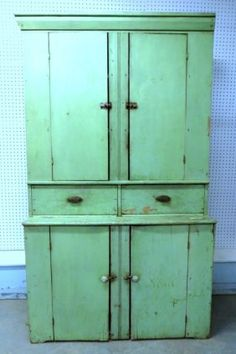 Primitive step-back cupboard having 2 solid doors over 2 drawers with iron pulls over 2 doors on base. Old green paint over other paint. Probably 3Q 19th century.