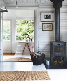 white wooden house. Love the sisal rugs and the vintage wood heater