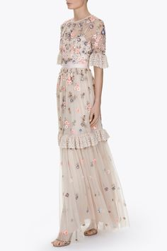 The Ditsy Scatter Gown has a flattering, fitted bodice with a fuller tulle skirt. The bodice fabrication is semi sheer tulle with an integrated camisole slip lining, finishing with our signature grosgrain trim at the waistband. Prairie inspired ruffle trims are featured on the sleeve and lower skirt in delicately embroidered tulle with lace inspired motifs. The Ditsy Scatter artwork is inspired by vintage ditsy fabric prints with pretty bunches of flowers. These are depicted in soft pastels…