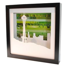 """Space Needle Shadowbox (by Amy Gibson) (1/2) - intricately hand-cut Seattle icon against an emerald-colored collage of discarded pages. Shadowbox is 10"""" x 10"""", frame is 0.75"""" thick and 1.75"""" deep. Can do other city landscapes!"""