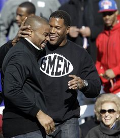 Former New York Giants player Michael Strahan, right, greets Giants defensive end Osi Umenyiora during a ceremony for the NFL football Super Bowl XLVI champions at City Hall in New York, Tuesday, Feb. 7, 2012. (AP Photo/Kathy Willens)