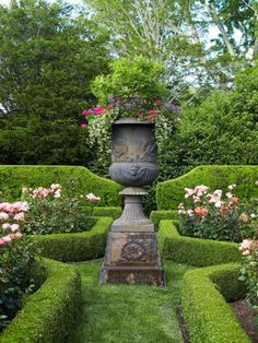 An enormous urn mounted on a pedestal displays a stately air. Surrounding structured boxwoods enhance the garden's focal point. - Traditional Home ® / Photo: Tria Giovan / Design: Jane E. Lappin and Arlene Gould