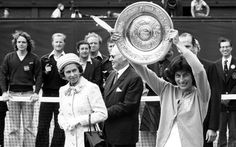 1 July 1977: The Queen watches as the Women's Singles Champion, Virginia Wade from Britain, shows her trophy to the crowd on the centre court at Wimbledon