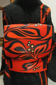 スカーレットオレンジに、木の実と木の葉をかたどったアールデコの装飾模様を思わせるモダンデザインが織り出された名古屋帯です。