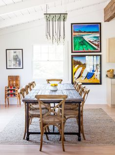 Rustic dining space with modern chandelier, colorful photographs on the wall, and wood table and chairs