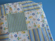Baby blanket Infant blanket Nursing blanket.One side with a white background with blue baby items.The other side strips checkers & baby toys by MissyCraftsandGoods on Etsy