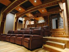 This home theater system features wood architecture, detailed ceiling design, wood floor, a bar area, stone walls and leather recliners.