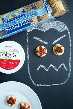 Toby's tofu spread on a rice cracker, hot sauce and olives. Perfect appetizer for any Halloween gathering!