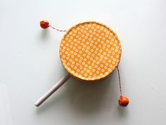 Glue two peanut butter lids together and sandwich pop stick and beaded string.
