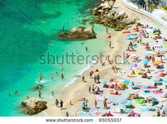 beach of the Cote d'Azur with tourists with sunbeds and umbrellas on the hot summer day