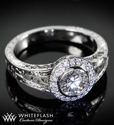 custom designed Halo Split Shank Diamond Engagement Ring is designed by Whiteflash.com. There are .10ctw in ACA diamond melee in halo, F/G in color and VS in clarity. The ring is hand engraved with a celtic scroll work on the split shank.